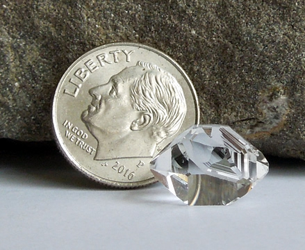 A dime next to the gem gives size.