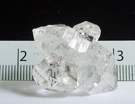 Three crystals in cluster with ruler.