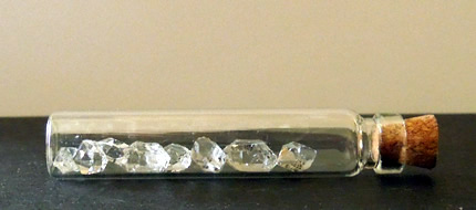 Eight Herkimer Diamonds in a glass vial.