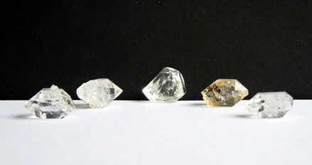 Five clear raw crystal points.