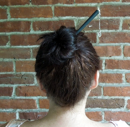 A hair pin holds a bun in place.