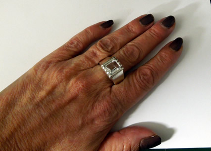 View of cut crystal ring on models hand.