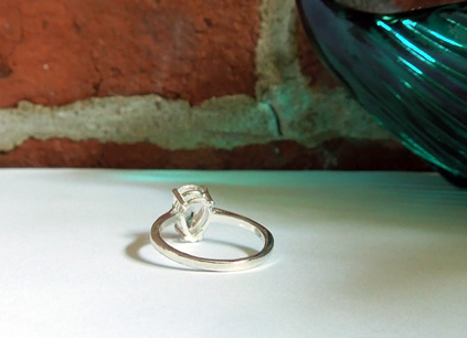 A 1.5 ct. pear cut crystal and silver ring.