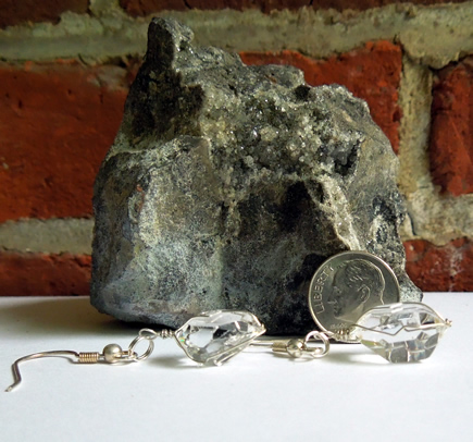 Herkimer matrix piece as backdrop to water clear crystal earrings.