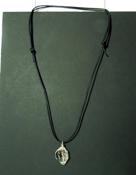 Pendant hangs from a black adjustable cord.