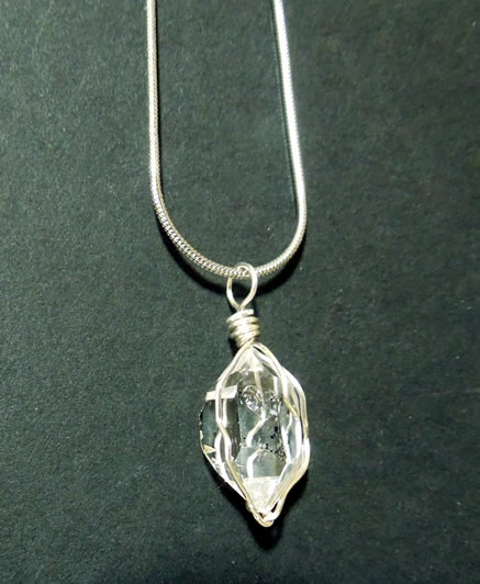 "An 18"" silver snake chain and Herkimer necklace."