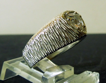 Side view of ring with trilliant cut crystal.