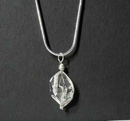 Raw, clear crystal pendant.