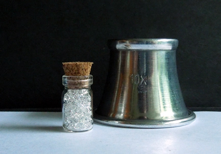 Images shows glass vial and loupe.